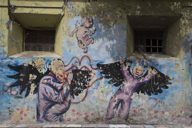 This April 16, 2015 photo shows a mural painted by inmates inside the courtyard of the now empty Garcia Moreno Prison, during a guided tour for the public in Quito, Ecuador. Psychologist Oscar Ortiz, who worked with the inmates behind these walls, organized local artists to collaborate with the prisoners to adorn the walls with paintings. (Photo by Dolores Ochoa/AP Photo)