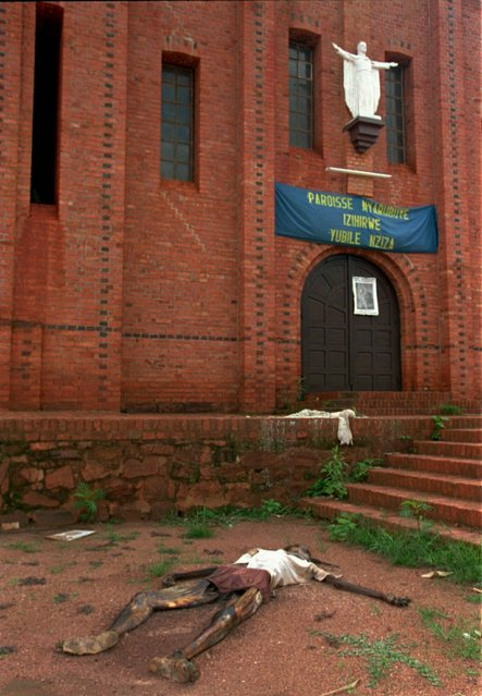 In this May 31, 1994, file photo, the body of a man lies at the entrance to a church in Nyarubuye, Rwanda. The scale of the killings in 1994 was unimaginable but the reporting and photographs taken at the time helped to inform the world of the horrors of the genocide. (Photo by Jean-Marc Bouju/AP Photo/File)