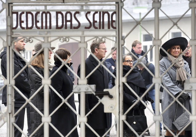 """Queen Maxima of the Netherlands. right,  passes the gate with the inscription """" Jedem das Seine'"""" ( To each his own) during a visit to the memorial of former Nazi concentration camp Buchenwald near Weimar, Germany. Wednesday, February 8, 2017. (Photo by Hendrik Schmidt/DPA via AP)"""