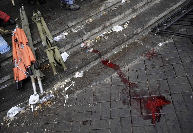 Blood and stretchers are seen on the pavement during clashes with riot police near Independence Square in Kiev February 20, 2014. At least 21 civilians were killed in fresh fighting in Kiev on Thursday, shattering an overnight truce declared by Ukrainian President Viktor Yanukovich, and a presidential statement said dozens of police were also dead or wounded. (Photo by Maks Levin/Reuters)