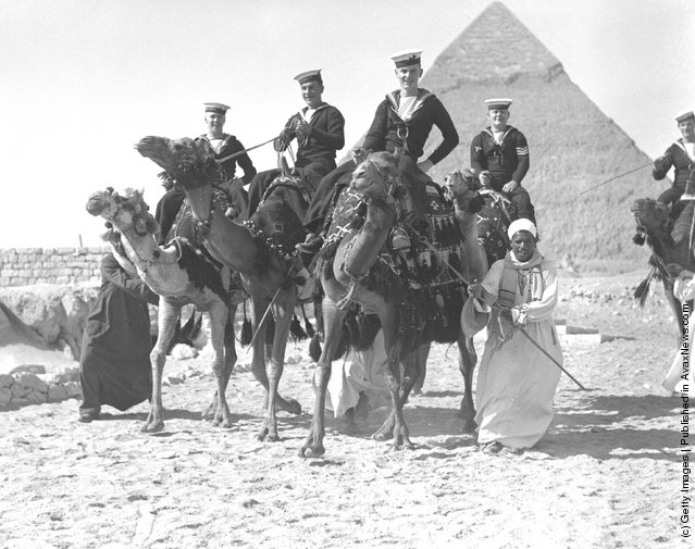 1937: Members of the British Navy enjoying a camel-ride in front of one of the pyramids, near Cairo, Egypt