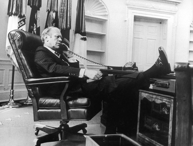 """President Gerald Ford, seated in an armchair with his foot on the desk, talking on the telephone in the oval office, Washington, D.C. circa 1974. Gerald Rudolph """"Jerry"""" Ford, Jr. was the 38th U.S. President serving from 1974 – 1977. (Photo by Consolidated News Pictures/Getty Images)"""