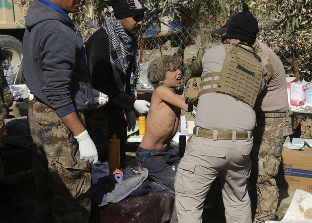 Army paramedics give first aid to displaced civilians, injured in IS mortar bombing, during fighting between Iraqi security forces and Islamic State militants, in the western side of Mosul, Iraq, Sunday, February 26. 2017. (Photo by Khalid Mohammed/AP Photo)