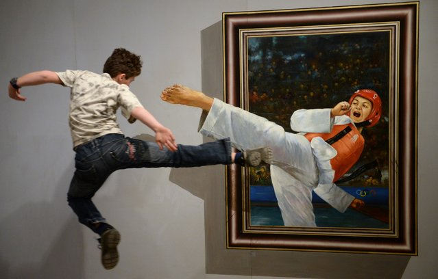 """A boy jump kicks towards a 3D artwork at the Chinese special exhibition """"Du bist die Kunst!"""" (lit. You are the art!) at Augustusburg Castle, in Augustusburg, Germany, 21 March 2014. The exhibition consists of 23 interactive images in which the visitor can stand and become part of the picture and runs until 22 June. (Photo by Hendrik Schmidt/EPA)"""