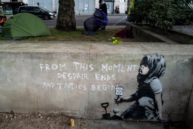"""Environmental protestors pack away their tents behind a new piece of street art which is believed to be by the artist known as """"Banksy"""" on April 26, 2019 in London, England. The artwork shows a child holding a small Extinction Rebellion sign crouching by a newly-planted seedling with the words """"From This Moment Despair Ends And Tactics Begin"""" It appeared after the closing ceremony of the Extinction Rebellion, the climate change protest movement that has disrupted central London for the past two weeks. (Photo by Leon Neal/Getty Images)"""