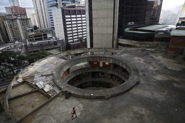 """A woman walks on a roof of the """"Tower of David"""" skyscraper in Caracas February 3, 2014. (Photo by Jorge Silva/Reuters)"""