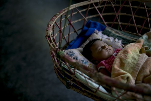 Meghla's 2 month old baby sleeps on March 7, 2017 in Khulna division, Bangladesh. 17-year-old Meghla married her 30-year-old husband, Liton, during an arranged marriage in 2015, while she was 15. The marriage was against the Bangladesh law at the time so Meghla's father forged her birth certificate, so she would be old enough for the marriage to be officially registered. Two months ago, Meghla gave birth to a baby girl, the next generation to the line of underage marriages in her family. Meghla's mother had married when she was 16-years-old and her grandmother was married when she was age 14. The age difference is good because I'm young and he can help guide me in life. If a girl is more than 20 and unmarried then she and her family are sexually harassed. When a girl is out with her husband, men won't dare harass her. When a girl turns down a boys dating proposals he will gossip about her and destroy her reputation. No one bothers to investigate if the gossip is true or not. It creates a huge problem for the girl and her family. That's why girls marry early here,Ó Meghla said. Despite having a husband, several boys who used to harass Meghla continued and threatened to kidnap her. Meghla had dreamed of being an engineer but since the accidental pregnancy, she has doubts in even going to university after graduation. Despite Liton's encouragement for Meghla to pursue a university degree, she forgoes her dream to bear the responsibilities as a mother. (Photo by Allison Joyce/Getty Images)