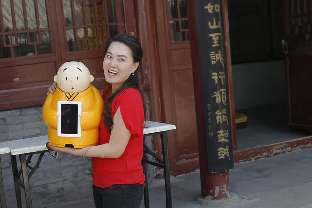 A visitor smiles as she holds Robot Xian'er which is placed in the main building of Longquan Buddhist temple for photograph by the temple's staff, on the outskirts of Beijing, April 20, 2016. (Photo by Kim Kyung-Hoon/Reuters)