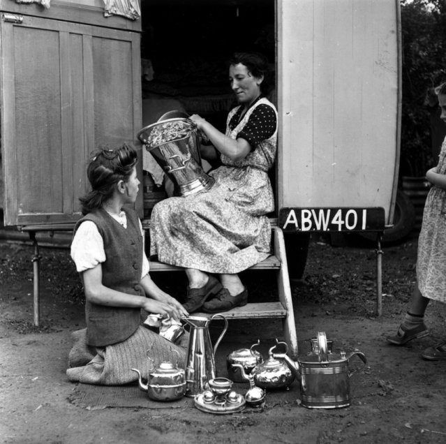Two Romany women polishing their silverware on the steps of their caravan at the Corke's Meadow encampment in Kent on July 28, 1951. (Photo by Bert Hardy/Getty Images)