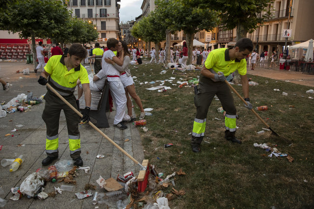 A couple kiss each other in the early hours as workers clean the streets the during the second day of the San Fermin Running of the Bulls festival on July 07, 2019 in Pamplona, Spain. (Photo by Pablo Blazquez Dominguez/Getty Images)