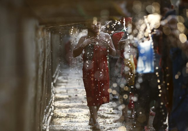 A devotee (C) smiles as she takes a holy bath at the Balaju Baise Dhara (22 water spouts) during the Baishak Asnan festival in Kathmandu, Nepal, April 22, 2016. (Photo by Navesh Chitrakar/Reuters)