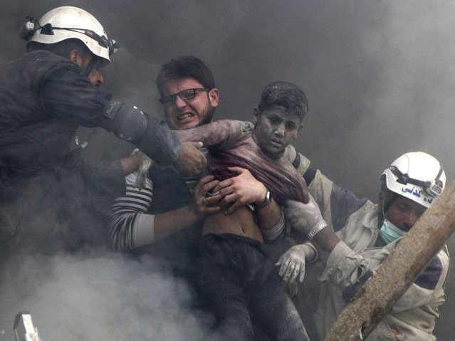 Men rescue a boy from under the rubble after what activists said was explosive barrels dropped by forces loyal to Syria's President Bashar Al-Assad in Al-Shaar neighbourhood of Aleppo, on April 7, 2014. (Photo by Hosam Katan/Reuters)