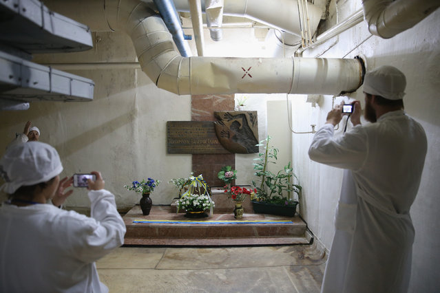Visitors photograph a memorial to worker Valery Khodemchuk at a wall that separates reactors three and four inside the former Chernobyl nuclear power plant on September 29, 2015 near Chornobyl, Ukraine. Khodemchuk was a circulating pump operator killed in the accident at reactor four and his body remains entombed inside the reactor four site. On April 26, 1986, technicians at Chernobyl conducting a test inadvertently caused reactor number four, which contained over 200 tons of uranium, to explode, flipping the 1,200 ton lid of the reactor into the air and sending plumes of highly radioactive particles and debris into the atmosphere in a deadly cloud that reached as far as western Europe. (Photo by Sean Gallup/Getty Images)