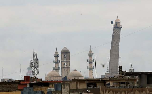 A black jihadist flag hangs from Mosul's Al-Habda minaret at the Grand Mosque, where Islamic State leader Abu Bakr al-Baghdadi declared his caliphate back in 2014, as Iraqi forces battle to drive out Islamic state militants from the western part of Mosul, Iraq, March 16, 2017. (Photo by Youssef Boudlal/Reuters)