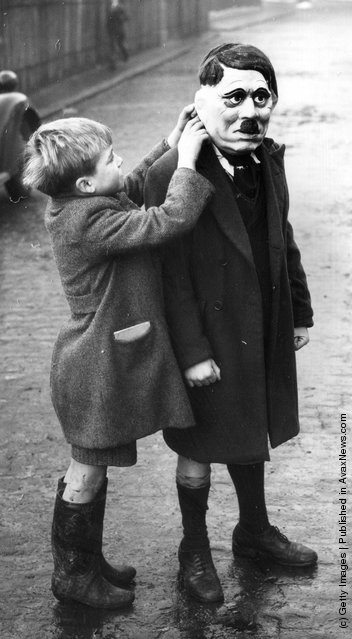 A young boy adjusts his friend's Adolf Hitler mask during a game on a street in King's Cross, London, 1938