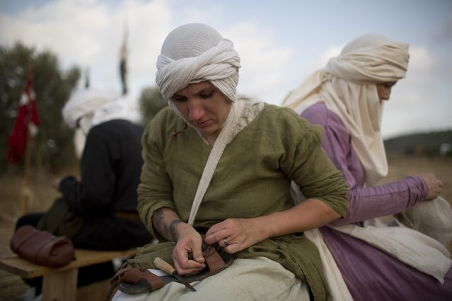 In this Thursday, July 2, 2015 photo, an Israeli member of a knight club fixes her sandal in the camp before marching 27 kilometers (17 miles) to the reenactment of the Battle of Hattin from the ancient northern city of Zippori to Horns of Hattin, northern Israel. (Photo by Oded Balilty/AP Photo)
