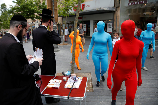 Members of the Prizma Ensemble wearing full solid-coloured bodysuits walk pest ultra orthodox jewish men as they take part in the 6th Jane's walk Jerusalem in Jerusalem Israel. May 6, 2016. (Photo by Baz Ratner/Reuters)