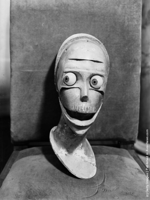 1933: A stylised sculpted head with staring eyes and gaping mouth