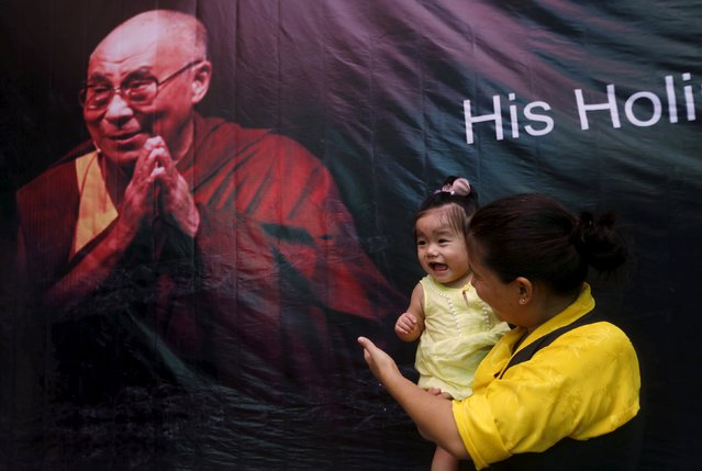 A Tibetan exile holds her daughter as she stands in front of a portrait of their spiritual leader, the Dalai Lama, during celebrations marking his 80th birthday at Majnu Ka Tila, a Tibetan refugee camp in New Delhi, India, July 6, 2015. (Photo by Adnan Abidi/Reuters)