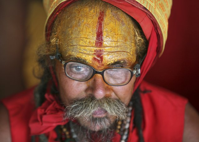 A Sadhu or a Hindu holy man, wearing a traditional tikka or a red mark on his forehead, waits to register for the annual pilgrimage to the Amarnath cave shrine, in Jammu, July 4, 2015. Thousands of Hindus trek annually to the holy cave of Amarnath, where they worship an ice formation that Hindus believe to be the symbol of Lord Shiva. (Photo by Mukesh Gupta/Reuters)