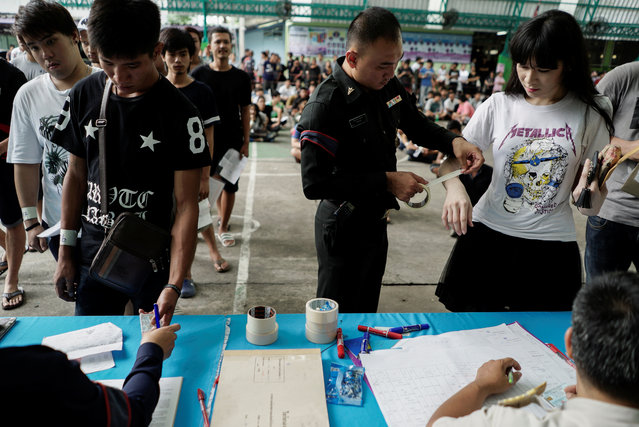 A military officer puts tape on the arm of a transgender woman during an army draft held at a school in Klong Toey, the dockside slum area in Bangkok, Thailand, April 6, 2017. (Photo by Athit Perawongmetha/Reuters)
