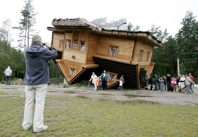 A man takes a picture as people wait in line to visit an upside down house built at the Centre of Education and Promotion of the Region in the village of Szymbark, northern Poland July 31, 2007. The upside down house created by Daniel Czapiewski is supposed to describe the times of the former communist era and the present times in which we live. (Photo by Peter Andrews/Reuters)