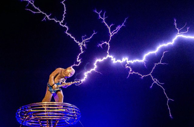 A picture made available on 07 May 2015 shows a man wearing an iron mesh suit while playing guitar with man-made lightening in a show for foreign visitors in Changle, Fujian province, China, 29 April 2015. Former electronics engineer Wang Zengxiang quit his well-paid job in 2012 to make equipments and started the band named Lei Ting Feng, or Lightening Craze, out of his love for Tesla coils. (Photo by Xiao Hai/EPA)
