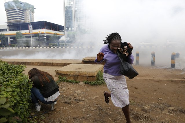 A woman runs while another woman ducks down to avoid teargas as police disperse supporters of the opposition Coalition for Reforms and Democracy (CORD), led by former Prime Minister Raila Odinga, during a demonstration against Independent Electoral and Boundaries Commission (IEBC) in downtown Nairobi, Kenya, 09 May 2016. (Photo by Dai Kurokawa/EPA)