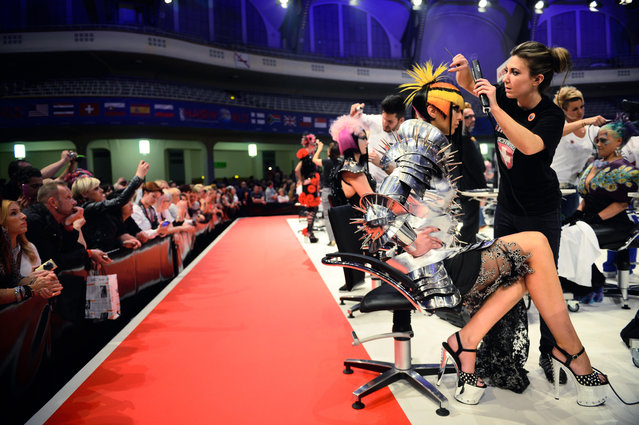 """A hairdresser styles her model during the contest """"Full Fashion Look"""" at the OMC Hairworld World Cup on May 4, 2014 in Frankfurt am Main, Germany. (Photo by Thomas Lohnes/Getty Images)"""