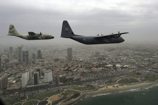 Israeli Air Force military cargo airplane C-130J Super Hercules, right, and Hercules C-130, left, fly over the city of Tel Aviv during an air show celebrating Independence Day Tuesday, May 6, 2014. Israel is celebrating its annual Independence Day, marking 66 years since the founding of the state in 1948. (Photo by Tsafrir Abayov/AP Photo)