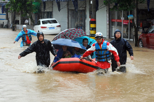 Rescuers use an inflatable boat to evacuate residents from a neighborhood flooded by heavy rains from Typhoon Chan-Hom in Shaoxing in eastern China's Zhejiang province Saturday, July 11, 2015. Some 1.1 million people were evacuated from coastal areas of Zhejiang and more than 46,000 in neighboring Jiangsu province ahead of the storm, the official Xinhua News Agency reported. (Photo by Chinatopix via AP Photo)