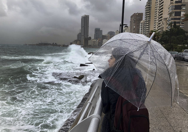 A Lebanese girl shelters for the rain, as she watches waves crash into the seawall on the Mediterranean Sea, in Beirut, Lebanon, Tuesday, January 8, 2019. A strong storm in Lebanon brought cold temperatures and snow to Lebanon's mountains and heavy rainfall, strong winds on the Lebanese coast. (Photo by Hussein Malla/AP Photo)