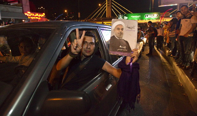 A man holds a picture of Iran's President Hassan Rouhani as he celebrates with others in the streets following a nuclear deal with major powers, in Tehran July 14, 2015. (Photo by Reuters/TIMA)