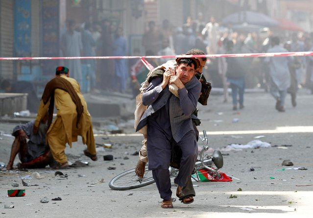 A man caries a wounded person to the hospital after a blast in Jalalabad, Afghanistan on August 19, 2019. (Photo by Reuters/Parwiz)