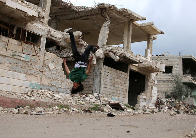 Parkour coach Ibrahim al-Kadiri, 19, demonstrates his Parkour skills near damaged buildings in the rebel-held city of Inkhil, west of Deraa, Syria, April 7, 2017. The team records their performances in photos and videos, which they post on social media. (Photo by Alaa Al-Faqir/Reuters)