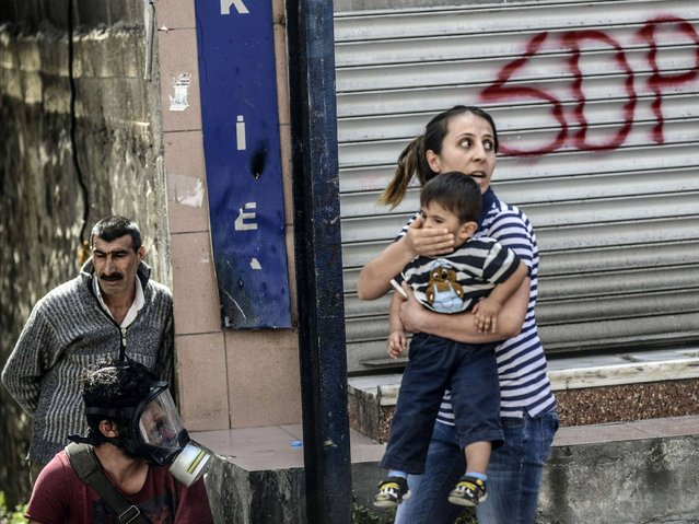 A woman holds her child as she tries to make her way through a street during clashes between Turkish riot police and protesters taking part in a demonstration against the recent mine accident in Soma, on May 22, 2014, in the Okmeydani district of Istanbul. One man was injured when Turkish riot police today fired tear gas and water cannon to disperse a group of Istanbul protesters hurling Molotov cocktails and stones. (Photo by Bulent Kilic/AFP Photo)