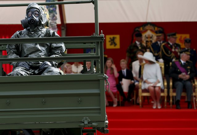 A soldier wearing personal protective equipment rides past Belgium's King Philippe and Queen Mathilde (R) during the traditional military parade in front of the Royal Palace in Brussels July 21, 2015. Belgium celebrates its National Day on Tuesday. (Photo by Francois Lenoir/Reuters)