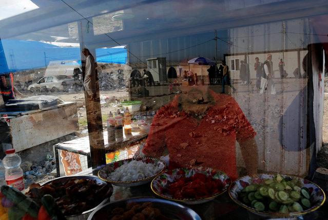 An Iraqi man sells food at a roadside stall outside Hammam al-Alil camp south of Mosul, Iraq, April 27, 2017. (Photo by Danish Siddiqui/Reuters)