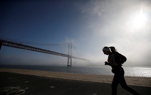 A runner is seen next to 25 April bridge in Lisbon, Portugal January 5, 2017. (Photo by Rafael Marchante/Reuters)