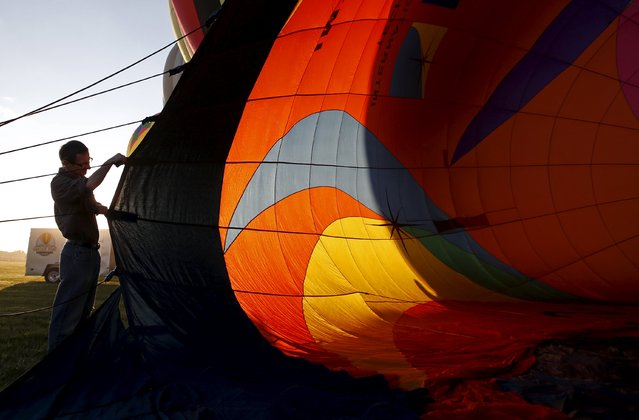 A crew member holds open a hot air balloon as it is inflated at sunrise on day one of the 2015 New Jersey Festival of Ballooning in Readington, New Jersey, July 24, 2015. (Photo by Mike Segar/Reuters)
