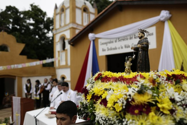 A wooden statue depicting St. Francisco Solano is displayed at the top of a religious float during a Mass marking the saint's feast day, in Emboscada, Paraguay, Friday, July 24, 2015. (Photo by Jorge Saenz/AP Photo)