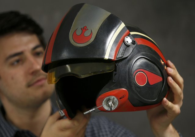 "A worker holds a replica of Poe Dameron's helmet from ""Star Wars: The Force Awakens"", in the Propshop headquarters at Pinewood Studios near London, Britain May 25, 2016. (Photo by Peter Nicholls/Reuters)"