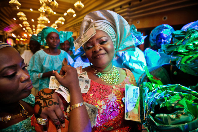 """""""Money dance in Lagos"""". Mother of the bride dancing during the reception of her daughter's wedding in Lagos, Nigeria. The other guests are throwing bank notes at her in a sign of respect. Photo location: Nigeria. (Photo and caption by Christophe Viseux/National Geographic Photo Contest)"""