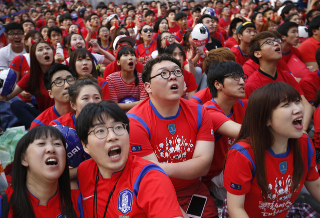 South Korean soccer fans react as they watch a live TV broadcast of their 2014 World Cup Group H soccer match against Russia, in Seoul June 18, 2014. (Photo by Kim Hong-Ji/Reuters)