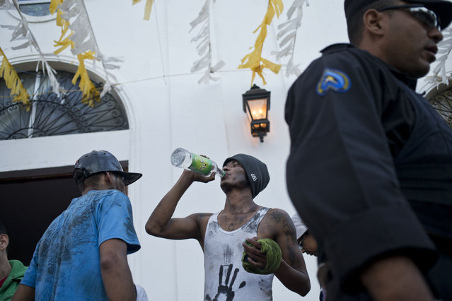A man drinks rum during the festivities in honor of Santo Domingo de Guzman in Managua, Nicaragua, Saturday, August 1, 2015. (Photo by Esteban Felix/AP Photo)