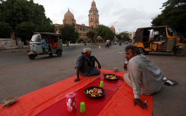 Men wait for sunset beside plates of food set out on a street side for passers by to be able to break fast on the first day of the Muslim holy month of Ramadan in Karachi, Pakistan June 7, 2016. (Photo by Akhtar Soomro/Reuters)