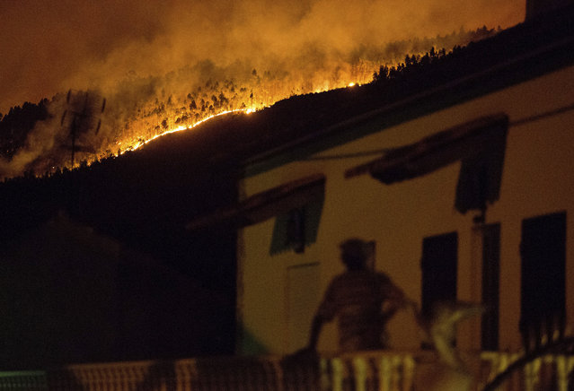 A man on the balcony of a house looks up at a forest fire raging on a hillside above the village of Avelar, central Portugal, before sunrise Sunday, June 18, 2017. A number of people have been killed in forest fires in central Portugal, many of them trapped in their cars as flames swept over a road Saturday evening. (Photo by Armando Franca/AP Photo)