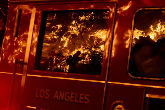 Flames are reflected on a LA City fire truck on Sepulveda Blvd. in the Sepulveda Pass as the Getty fire as it burns in Los Angeles, Calif., on October 28, 2019. (Photo by Brian van der Brug/Los Angeles Times via Getty Images)