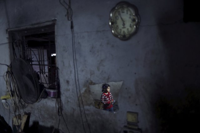 A Palestinian girl is reflected in a mirror as she stands at her family's house lit by a torch during a power cut in the northern Gaza Strip March 25, 2015. (Photo by Mohammed Salem/Reuters)