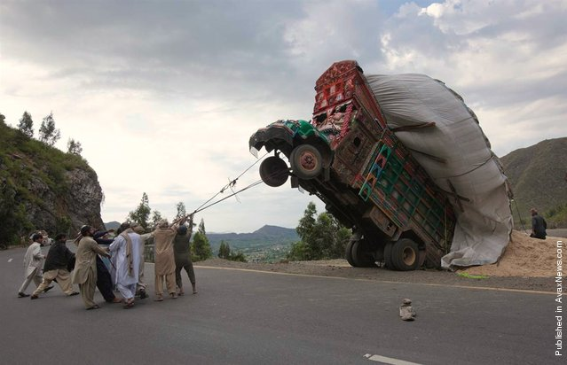 Men use ropes to try and right a supply truck overloaded with wheat straw along a road in Dargai, in the Malakand district, about 100 miles northwest of Pakistan's capital Islamabad, on April 13